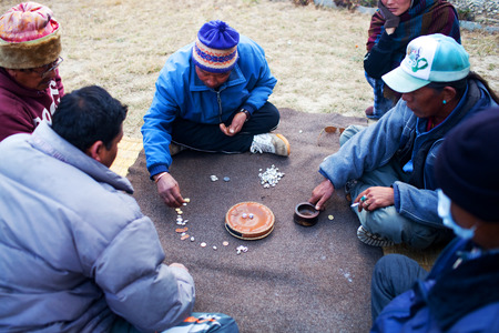 gambling counter: GHOREPANI, ANNAPURNA CONSERVATION AREA, NEPAL - DECEMBER 19: Villagers men and porters sitting on grass and  playing the Yam game. Yam - traditional Tibetan table game.