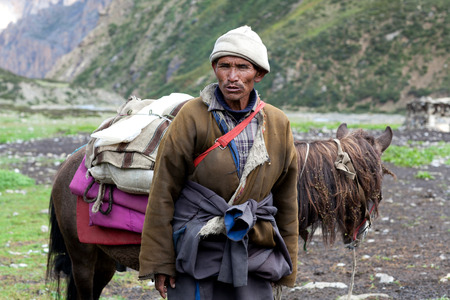 herdsman: SHEY, NEPAL - SEPTEMBER 4: Tibetan nomad with horse working at Shey Gompa on September 4, 2011 in Shey village, Nepal
