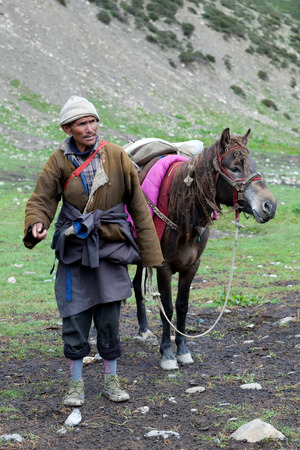 drover: SHEY, NEPAL - SEPTEMBER 4: Tibetan nomad with horse working at Shey Gompa on September 4, 2011 in Shey village, Nepal