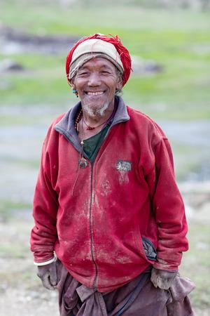 indigence: SHEY, NEPAL - SEPTEMBER 4: Smiling Tibetan man repairing the ancient Shey Gompa on September 4, 2011 in Shey village, Nepal