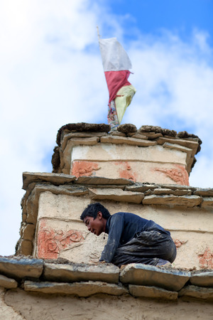 gompa: SHEY, NEPAL - SEPTEMBER 4: Young Tibetan man repairing the ancient Shey Gompa on September 4, 2011 in Shey village, Nepal