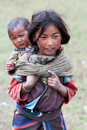 DHO TARAP, NEPAL - SEPTEMBER 10: Tibetan girl with her baby brother walkig on the road on September 10, 2011 in Dho Tarap village, Upper Dolpo, Nepal