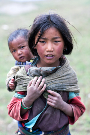indigence: DHO TARAP, NEPAL - SEPTEMBER 10: Tibetan girl with her baby brother walkig on the road on September 10, 2011 in Dho Tarap village, Upper Dolpo, Nepal