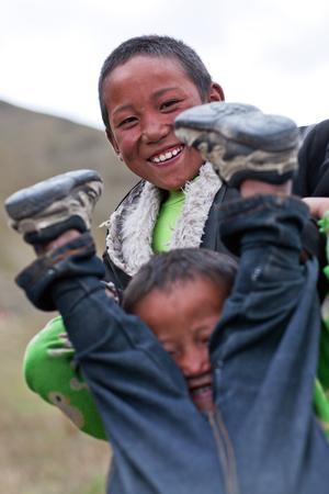 indigence: DHO TARAP, NEPAL - SEPTEMBER 10: Tibetan boys playing during Full Moon Festival on September 10, 2011 in Dho Tarap village, Dolpo, Nepal