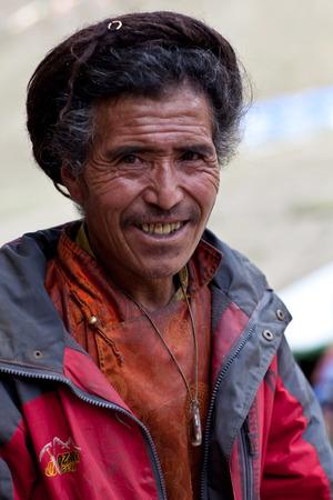 gompa: DHO TARAP, NEPAL - SEPTEMBER 10: Tibetan man in national clothesl walking around gompa on September 10, 2011 in Dho Tarap village, Upper Dolpo, Nepal Editorial
