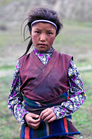 DHO TARAP, NEPAL - SEPTEMBER 10: Nepalese girl in traditional clothes working in the field on September 10, 2011 in Dho Tarap, Upper Dolpo, Nepal Editorial