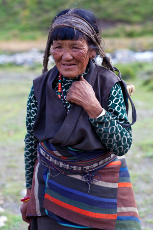 DHO TARAP, NEPAL - SEPTEMBER 10: Aged Tibetan woman in national clothes working in the fields on September 10, 2011 in Dho Tarap Village, Dolpo district, Nepal