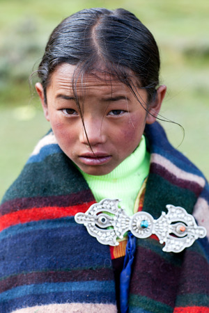 DHO TARAP, DOLPO, NEPAL - SEPTEMBER 11: Tibetan girl in national clothes poses for a photo during Dho Tarap Full Moon Festival on September 11, 2011 in Dho Tarap village, Dolpo district, Nepal Editorial