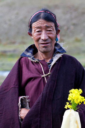drover: DHO TARAP, NEPAL - SEPTEMBER 11: Tibetan nomad with offering flowers poses for a photo during Dho Tarap Full Moon festival on September 11, 2011 in Dho Tarap village, Upper Dolpo, Nepal