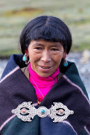 DHO TARAP, DOLPO, NEPAL - SEPTEMBER 11, 2011: Tibetan woman in national clothes poses for a photo during Dho Tarap Full Moon Festival in Dho Tarap village, Dolpo district, Nepal Editorial