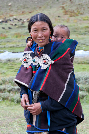 DHO TARAP, DOLPO, NEPAL - SEPTEMBER 11: Tibetan woman in national clothes with her baby poses for a photo during Dho Tarap Full Moon Festival on September 11, 2011 in Dho Tarap village, Dolpo district, Nepal