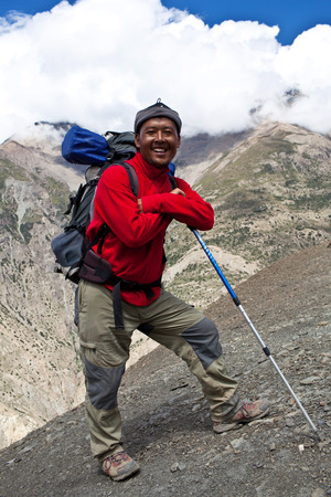 sherpa: UPPER DOLPO, NEPAL - SEPTEMBER 16: Smiling Sherpa trekking guide walking to the pass on September 16, 2011 in Upper Dolpo restricted area, Nepal