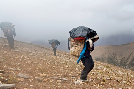 carrying heavy: Porters carrying heavy load across Himalayan pass on September 12, 2011 in Upper Dolpo restricted area, Nepal