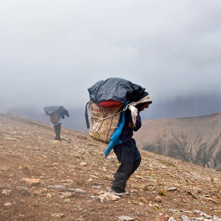 traditional climbing: Nepalese Porters carrying heavy load across Himalayan pass on September 12, 2011 in Upper Dolpo restricted area, Nepal