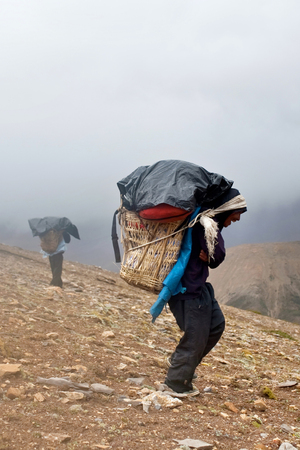 hard stuff: Nepalese Porters carrying heavy load across Himalayan pass on September 12, 2011 in Upper Dolpo restricted area, Nepal