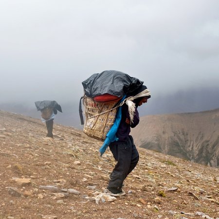 DOLPO, NEPAL - SEPTEMBER 12: Porters carrying heavy load across Himalayan pass on September 12, 2011 in Upper Dolpo restricted area, Nepal