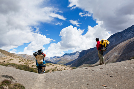 SHEY LA, NEPAL - SEPTEMBER 13: Nepalese porters walking across mountain pass on September 13, 2011 in the Nepal Himalaya