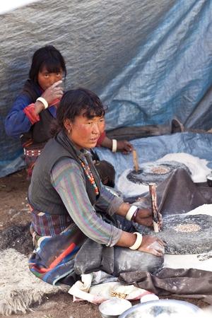 indigence: CHARKA, NEPAL - SEPTEMBER 14: Tibetan women cooking Tibetan dish Tsampa during Full Moon Festival on September 14, 2011 in Charka Village, Dolpo district, Nepal