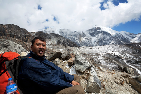 sherpa: Sherpa trekking guide with backpack resting on the mountain pass on March 14, 2010 in Sagarmatha National Park, Nepal Himalaya Editorial