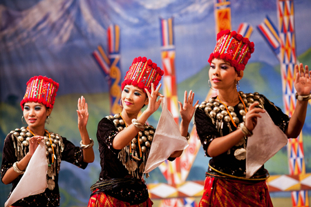 YANGON, MYANMAR - JANUARY 25, 2011: Burmese girls performing traditional Kachin dance in Karaweik Hall.