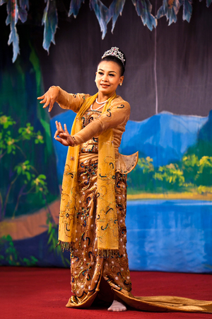 showgirl: YANGON, MYANMAR - JANUARY 25, 2011: Girl performing traditional Burmese dance on the evening show in Karaweik Hall. Editorial