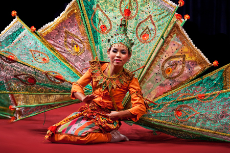 thai dancing: YANGON, MYANMAR - JANUARY 25, 2011: Burmese girl performing traditional Peakock Dance on the evening show in Karaweik Hall. Editorial