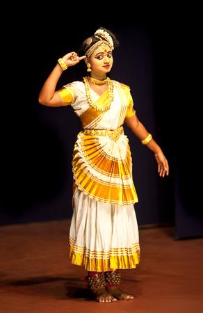 india dance: COCHIN, INDIA - FEBRUARY 17, 2010: Beautiful Indian girl dancing Mohinyattam Dance of enchantress in Fort Cochin, South India. Mohiniyattam is traditional South Indian dance from Kerala Editorial