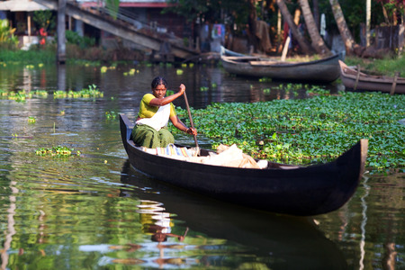 alleppey: ALLEPPEY, INDIA - FEBRUARY 13: Woman traveling in wooden boat on Kerala backwaters on February 13, 2010 in Alleppey, Kerala State, South India