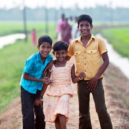 allepey: Smiling Indian children walking on the road over green fields on February 13, 2010 in Allepey, India Editorial