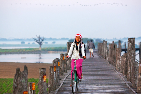 bycicle: Girl with bycicle riding on famous U-Bein teak bridge on January 13, 2011 in Amarapura, Myanmar.