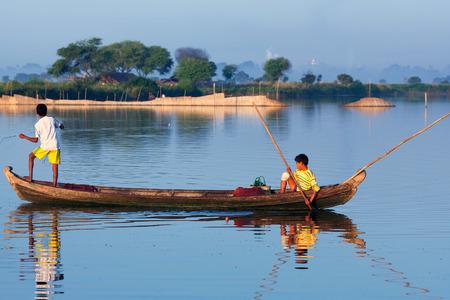 boatman: Burmese boys fishing on Thaungthaman Lake on January 13, 2011 in Amarapura, Mandalay Division, Myanmar. Editorial