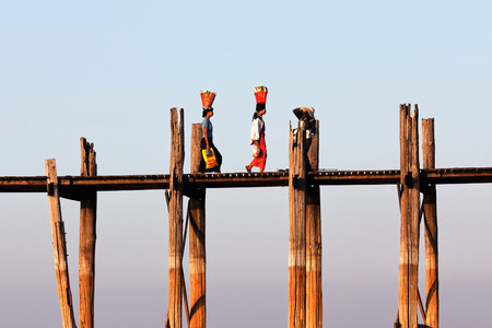 famous women: Women walking on famous U-Bein teak bridge on January 13, 2011 in Amarapura, Myanmar. Editorial