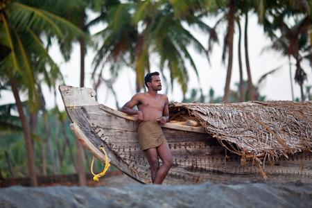 south india: VARKALA, INDIA - JANUARY 30, 2010: Indian fisherman standind near his wooden boat at sea shore in Varkala village, Kerala, South India