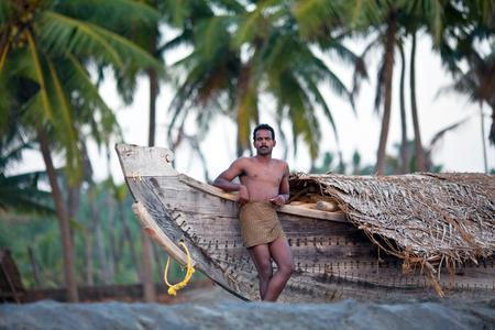 india fisherman: VARKALA, INDIA - JANUARY 30, 2010: Indian fisherman standind near his wooden boat at sea shore in Varkala village, Kerala, South India