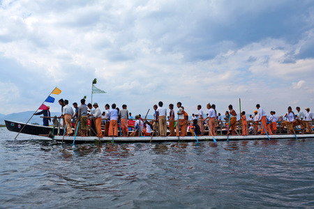 daw: NYAUNG SHWE, MYANMAR - JANUARY 17: Team of Burmese leg rowers crossing the lake during annual Buddhist Phaung Daw U festival on January 17, 2011 on Inle Lake, Shan State, Myanmar.