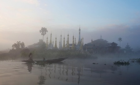 boatman: Ancient pagoda and monastery at sunrise on Inle lake, Shan state, Myanmar Stock Photo