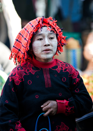 local festivals: SAMKAR, MYANMAR - JANUARY 15: Pa-O tribal woman in native costume walking at weekly market on January 15, 2011 in Samkar Village, Shan state, Myanmar