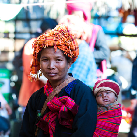 pao: SAMKAR, MYANMAR - JANUARY 15: Pa-O tribal woman in native costume with baby walking at weekly market on January 15, 2011 in Samkar Village, Shan state, Myanmar
