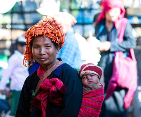 local festivals: SAMKAR, MYANMAR - JANUARY 15: Pa-O tribal woman in native costume with baby walking at weekly market on January 15, 2011 in Samkar Village, Shan state, Myanmar