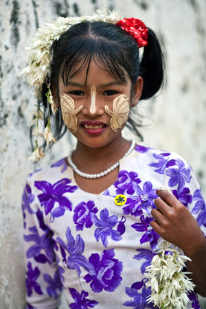 thanaka: Smiling Burmese girl with thanaka paste on her face poses for a photo on January 09, 2011 in Mandalay, Myanmar. Thanaka is a yellowish-white cosmetic paste made from ground bark. Burmese women will vouch that thanaka helps remove acne, promotes smooth ski