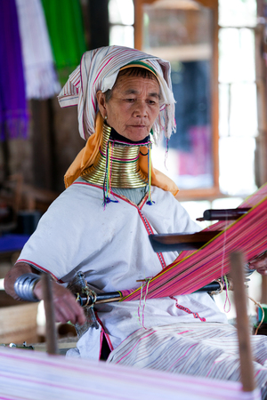 necked woman: Padaung Tribal woman weaving on January 5, 2011 in Myinkaba Village, Bagan, Myanmar. The Padaung-Karen long-necked tribe women are minority of Myanmar exploited for tourism reasons.