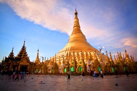 pilgrim journey: YANGON, MYANMAR - JANUARY 3, 2011: Pilgrims walking around golden Shwedagon Pagoda at sunrise in Yangon, Myanmar. The pagoda is situated on Singuttara Hill and dominates the Yangon skyline.