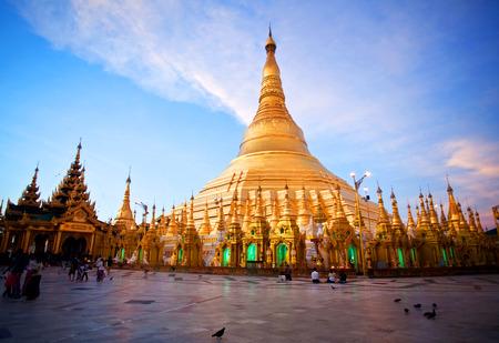YANGON, MYANMAR - JANUARY 3, 2011: Pilgrims walking around golden Shwedagon Pagoda at sunrise in Yangon, Myanmar. The pagoda is situated on Singuttara Hill and dominates the Yangon skyline.