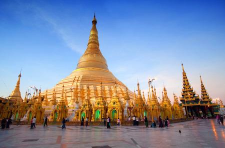 january sunrise: YANGON, MYANMAR - JANUARY 3, 2011: Pilgrims walking around golden Shwedagon Pagoda at sunrise in Yangon, Myanmar. The pagoda is situated on Singuttara Hill and dominates the Yangon skyline.