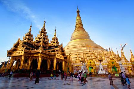 january sunrise: YANGON, MYANMAR - JANUARY 3, 2011: Pilgrims walking around Shwedagon Pagoda at sunrise in Yangon, Myanmar. The pagoda is situated on Singuttara Hill and dominates the Yangon skyline. Editorial