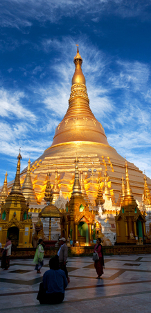 pilgrim journey: Pilgrims walking around golden Shwedagon Pagoda at sunrise in Yangon, Myanmar. The pagoda is situated on Singuttara Hill and dominates the Yangon skyline.