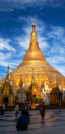 Pilgrims walking around golden Shwedagon Pagoda at sunrise in Yangon, Myanmar. The pagoda is situated on Singuttara Hill and dominates the Yangon skyline.