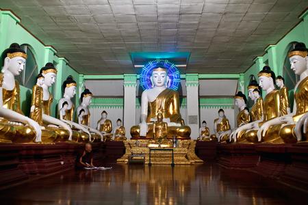 YANGON, MYANMAR - JANUARY 26, 2011: An unidentified Buddhist monk praying at Shwedagon Pagoda in Yangon, Myanmar Editorial