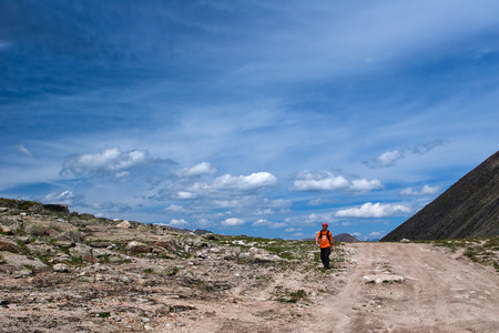 altay: ALTAY, RUSSIA - JULY 23, 2007: Hiker walking on the road to Ukok plateau in the Altay Mountains, Russia