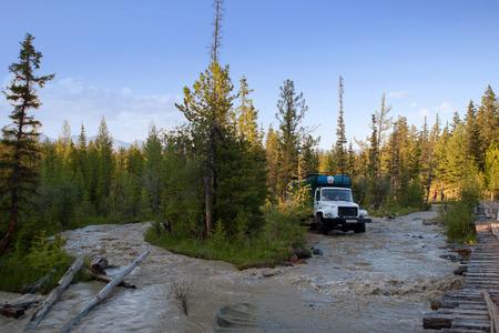 aktru: Vehicle driving over river in Siberia, Altay, Russia